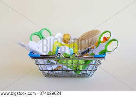 Shopping Basket With Baby Care Items - Scissors, Hairbrushes, Pacifiers, Thermometer, Cotton Pads An