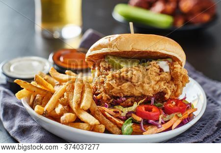 fried chicken sandwich with coleslaw and french fries