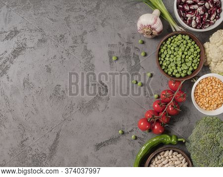 Organic Vegetables And Assorted Beans On A Grey Background.