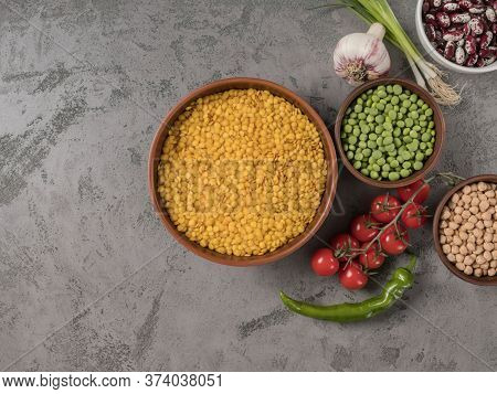 Legumes And Fresh Vegetables On A Gray Background.