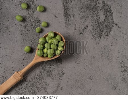 Young Green Peas In A Wooden Spoon On A Gray Background.