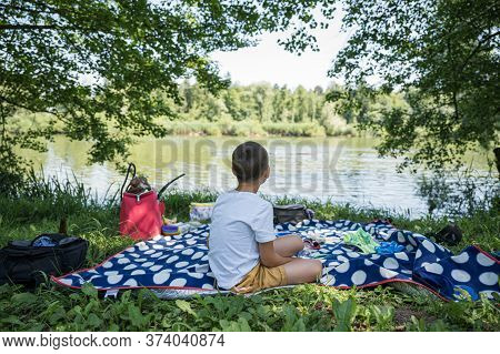 View From Behind Of A Boy Sitting On Polka Dot Picnic Blanket In A Grass By A Lake.