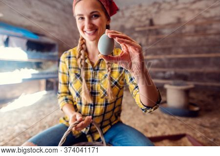 Happy farmer woman showing egg she just collected in a henhouse