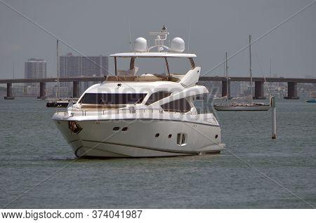 Small White Luxury Motor Yacht Idling On The Florida Intra-coastal Waterway Off Of Miami Beach Waiti