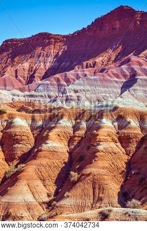 Arizona and Utah, USA. Paria Canyon-Vermilion Cliffs Wilderness Area. Huge slopes of red sandstone, striped from various inclusions of light rocks. The concept of active, extreme and photo tourism
