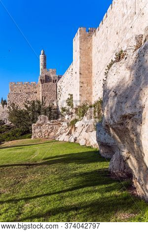 Hot summer sunset. Ancient Citadel - Tower of David. Adorable green lawn growing under ancient walls. The fortress wall of old Jerusalem. The concept of historical, pilgrim and photo tourism