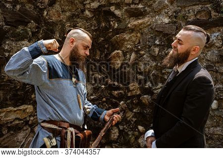A Man In Viking Clothes Challenges His Alter Ego Who Derides Him In Contemporary Clothes, The Same M
