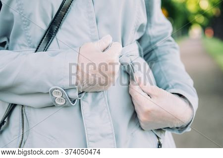 A Girl In Medical Gloves Tightens The Belt Of A Spring Coat On The Street.