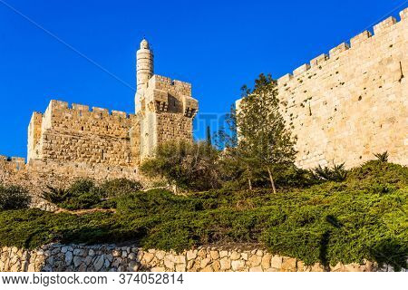 Hot summer sunset. Monumental walls of Jerusalem. The height of the walls is 12 meters. Ancient Citadel - Tower of David. The concept of historical, religious, pilgrim and photo tourism