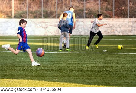 Hydra, Greece - October 4th, 2018: One Kid Playing Football In A Soccer Field With The Barcelona Shi