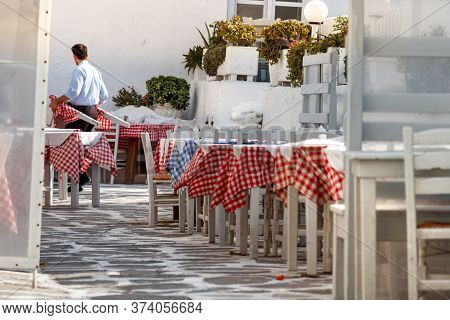 Mykonos, Greece - October 12th, 2018: A Male Waiter Carrying On - Moving A Table Preparing The Resta
