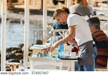 Mykonos, Greece - October 12th, 2018: A Male Waiter Clearing A Table Outdoors At A Greek Tavern In T