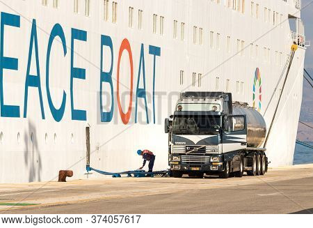 Corfu, Greece - October 1th, 2018: A Seaman Worker And A Volvo Truck Cistern Refueling A Cruise Ship