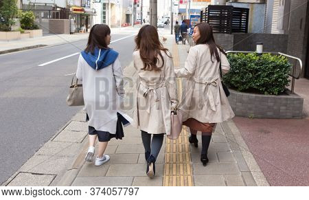 Nagasaki, Japan - March 26th, 2017: Three Japanese Girls Walking On The Sidewalk, Two Of Them Wearin
