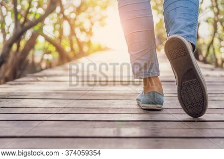 Man Is Walking On Small Wood Bridge To Nature Walk Way With Sunlight Flare.