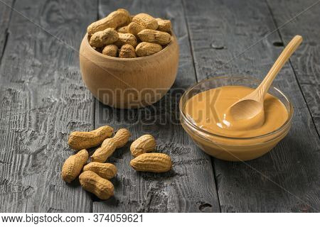 Glass Bowl With Peanut Paste And Wooden Bowl With Peanut Fruit. Natural Peanut Cream.