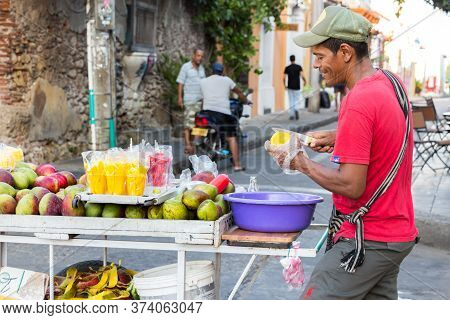 Cartagena, Colombia - January 23th, 2018: A Fruit Street Vendor Cutting Mango Standing On The Street