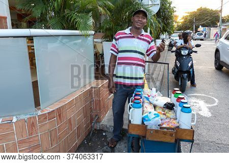 Cartagena, Colombia - January 23th, 2018: A Colombian Vendor Posing Showing A Cup Of Traditional Tin