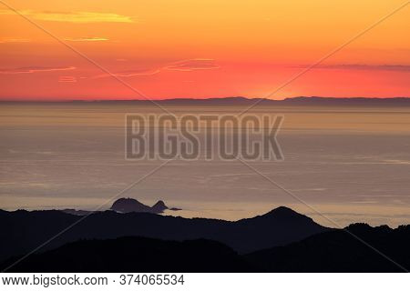 Sunset Over Ile Rousse And The Mediterranean Sea On The West Coast Of Corsica With The Silhouetted C