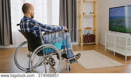 Paralyzed And Depressed Young Man In Wheelchair Watching Tv.