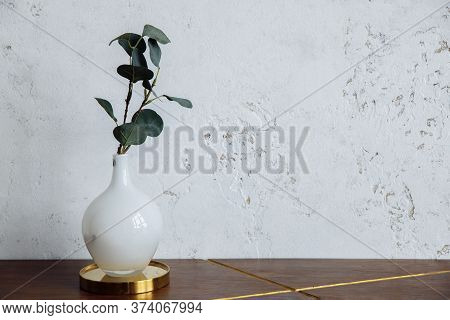 A Cherry Branch With Green Leaves Stands In A White Frosted Round Vase. The Vase Sits On A Wooden Ta