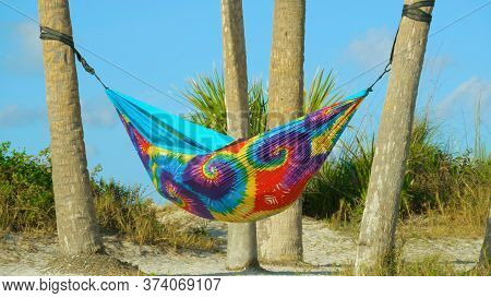 Hammock Of Rainbow Colors Hanging Between The Palm Trees On Beach. People On Summer Vacation Relaxin