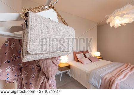 Fashionable handbag hanging on a clothesline.