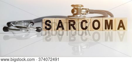Sarcoma The Word On Wooden Cubes, Cubes Stand On A Reflective White Surface, On Cubes - A Stethoscop