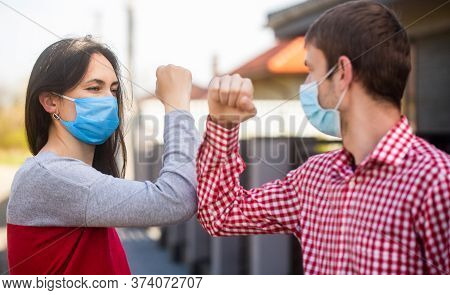Social Distancing. Girl And Guy Greeting With Elbows Outdoors. New Real Life. Coronavirus Quarantine