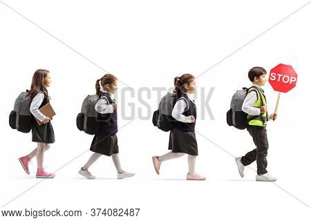 Full length profile shot of a schoolboy walking with a safety vest and a stop sign and other children following behind isolated on white background