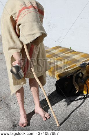 Wanderer With A Stick And Barefoot Asks For Alms Under A Dirty And Ruined Blanket