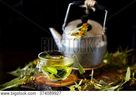 Selective Focus. A Cup Of Linden Tea. Kettle With Tea. Linden Tea Pours From The Kettle. Healthy Dri