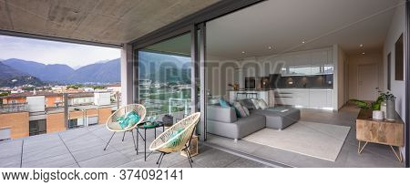 Large terrace with two armchairs or chairs. You can also see the interior of the modern apartment with its open kitchen and its living room or lounge.