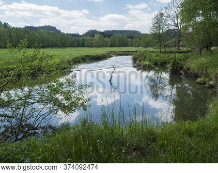 Idyllic Landscape Of Winding River Stream Meander At Lush Green Meadow With Deciduous Tree Forest, B