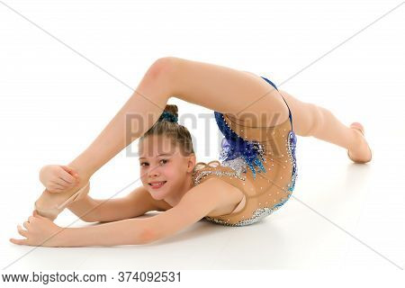 Gymnast Girl Lying On Her Stomach With Legs Up, Flexible Girl Doing Gymnastic Exercises. Looking At