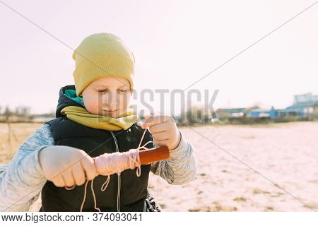 Caucasian Boy Of 6-7 Years Old Takes Up A Twine From A Kite. Pleasant Activity In Fresh Air On A Sun