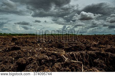 Agriculture Plowed Field. Black Soil Plowed Field With Stormy Sky. Dirt Soil Ground In Farm. Tillage