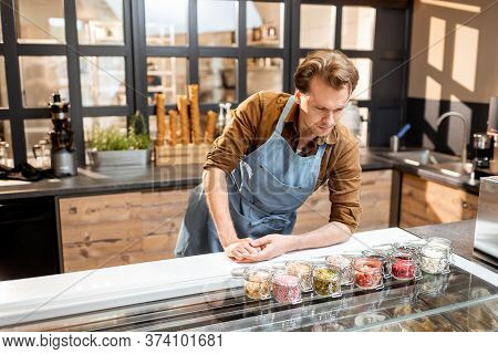 Confectioner Trying Different Food Additives In The Form Of Topping For Ice Cream At The Counter Of