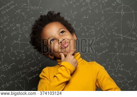 Clever Black Child Thinking On Chalkboard Background With Science Formulas