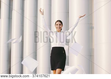 Happy Beautiful Business Woman In Suit Throw Up Papers Away And Smile Outdoors. Cheerful Young Attra