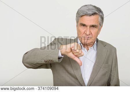 Portrait Of Stressed Senior Businessman Giving Thumbs Down