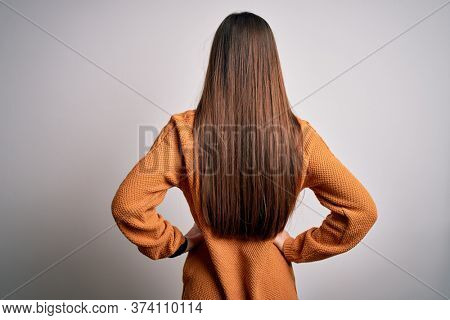 Young beautiful woman with blue eyes wearing casual sweater standing over white background standing backwards looking away with arms on body