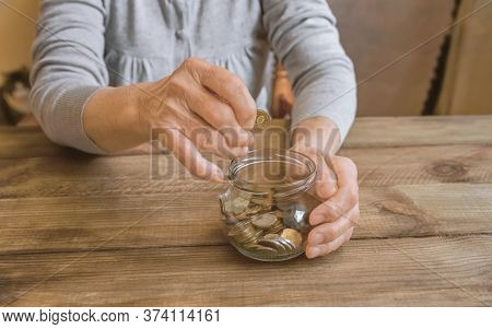 Old Wrinkled Hand Holding Jar With Coins, Empty Wallet, Wooden Background. Elderly Woman Throws A Co