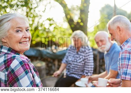 Group of seniors in the garden in retirement home drinking coffee together
