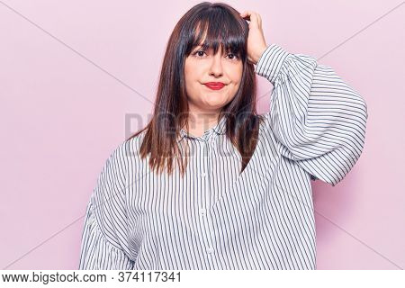 Young plus size woman wearing casual clothes confuse and wonder about question. uncertain with doubt, thinking with hand on head. pensive concept.