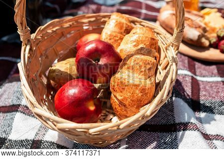 Picnic Bread, Croissant Basket With Fruit On Cloth With Bright Sunlight. Croissant, Honey, Strawberr