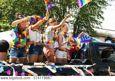 Babylon, New York, Usa - 28 June 2020: Young Girls Waving Flags And Celebrating While Riding In The