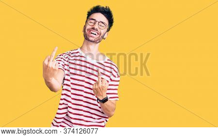 Young hispanic man wearing casual clothes showing middle finger doing fuck you bad expression, provocation and rude attitude. screaming excited