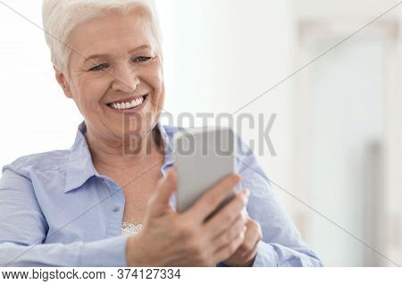 Online Banking App. Happy Senior Woman Using Smartphone, Checking Her Bank Account Balance From Home