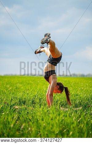 Girl Acrobat Performs A Handstand. The Model Stands On Her Hands, Doing Gymnastic Splits Against The